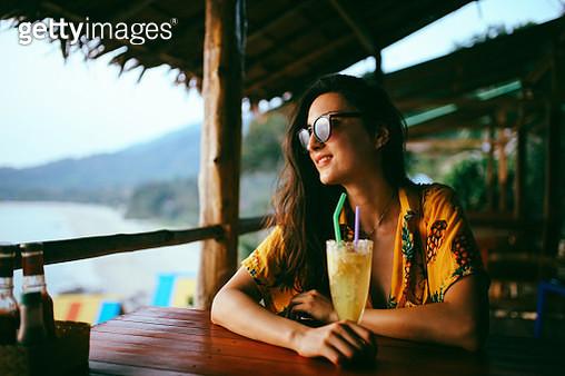 Young woman having fresh fruit drinks on the island of Koh Lanta, Thailand - gettyimageskorea