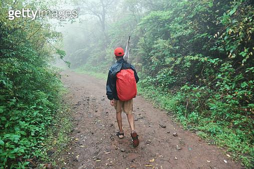 Teenage boy hiking in monsoon season in Lonavala near Mumbai in Maharashtra, India - gettyimageskorea