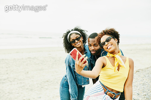 Smiling friends taking selfie with smart phone on beach - gettyimageskorea