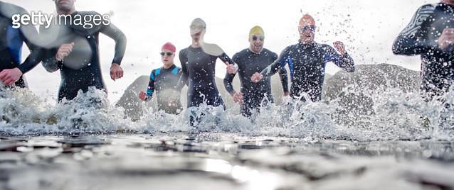 Triathletes emerging from water - gettyimageskorea