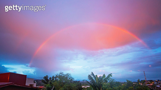 A beautiful rainbow shines in front of a pink sky at sunset - gettyimageskorea