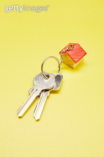 High angle view of keyring with a small house on colored background - gettyimageskorea