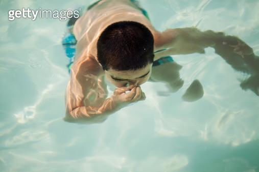 Child holding breath underwater in pool - gettyimageskorea