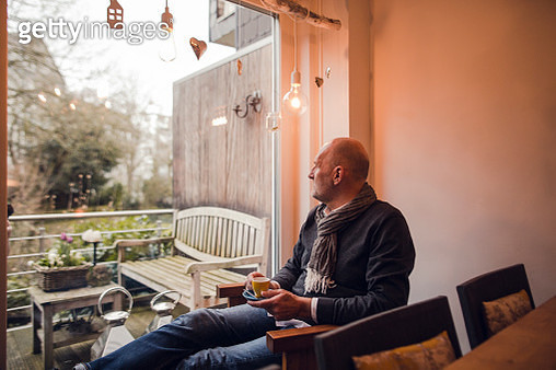 Senior man sitting at home, drinking coffee - gettyimageskorea