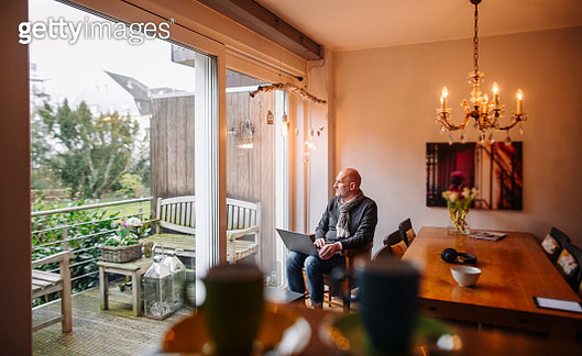 Senior man sitting at home, using laptop - gettyimageskorea