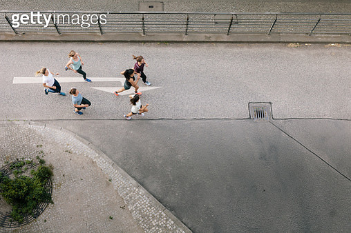 An aerial view of a women's only fitness group running together through the city. - gettyimageskorea