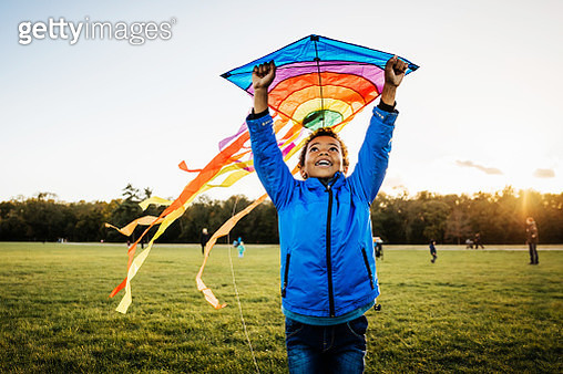 A young boy out in a park enjoying learning how to fly a kite. - gettyimageskorea