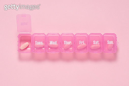 Pink Colored Weekly Pill Box on Blue Background. - gettyimageskorea