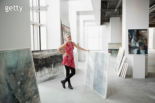 Portrait art dealer with painting in art gallery - gettyimageskorea