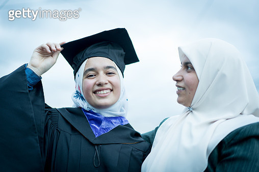 Portrait of Muslim Arabic teen girl after graduation ceremony with mother - gettyimageskorea