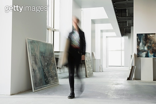 Art dealer walking with paintings in art gallery - gettyimageskorea