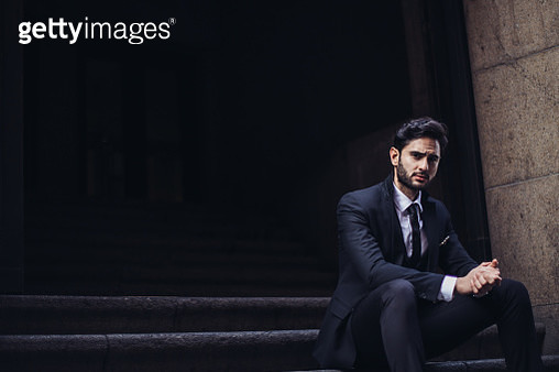 Man in formal suit sitting on the steps - gettyimageskorea