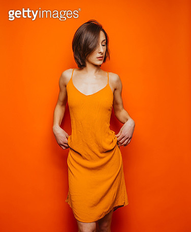 Woman in orange dress on orange background - gettyimageskorea