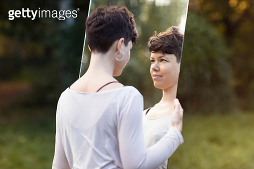 Smiling woman with short hair looking in mirror while standing at park - gettyimageskorea