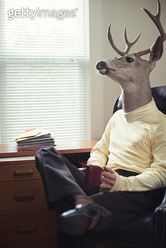 A buck / deer head on a mans body sits in an office chair next to a desk with a stack of papers.  He looks out his window while drinking a cup a coffee.  Vertical with copy space. - gettyimageskorea