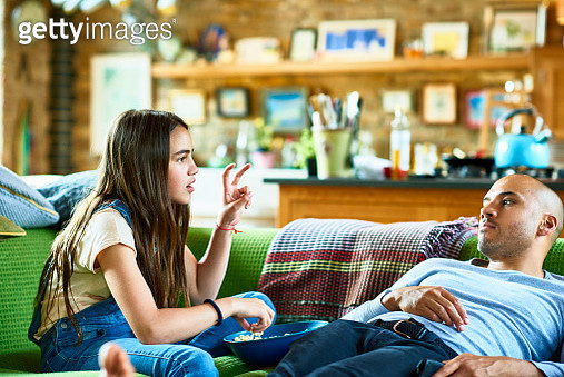 Father and daughter relaxing on sofa - gettyimageskorea