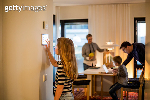 Girl using digital tablet on wall with family in background at smart home - gettyimageskorea