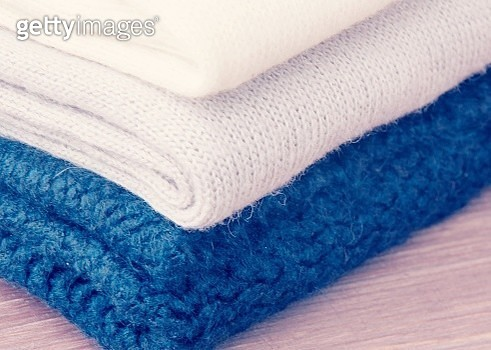 Close-Up Of Sweaters Stacked On Table - gettyimageskorea