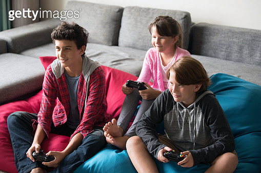 Kids playing video games together at home. - gettyimageskorea