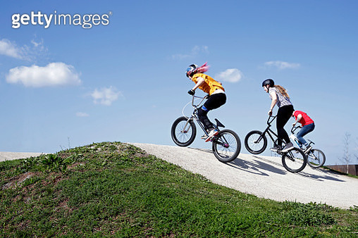 Dynamic view of female cyclists racing up steep ramp on skate park, competition, race, vitality - gettyimageskorea