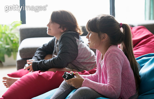 Brother and sister playing video games togehter - gettyimageskorea