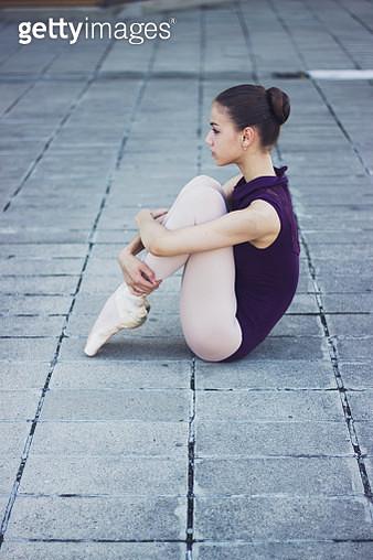 Ballet dancer (18-19) sitting on pavement - gettyimageskorea