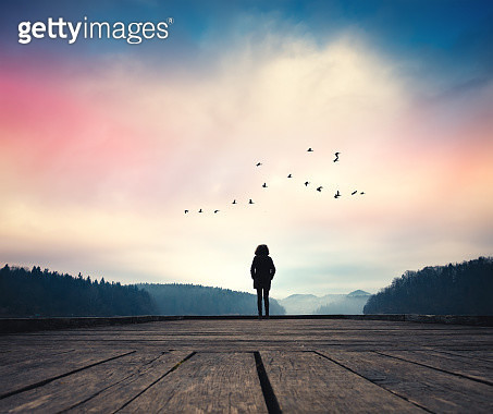 Woman standing on jetty and watching sunrise by the lake. - gettyimageskorea