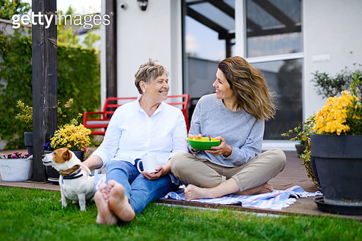 Portrait of woman with senior mother and pet dog sitting outdoors in garden, resting. - gettyimageskorea