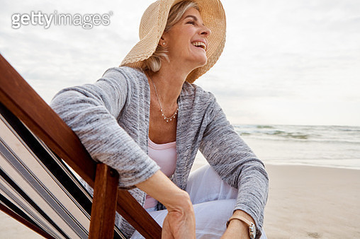 Cropped shot of an attractive middle aged woman sitting on a lounger at the beach - gettyimageskorea