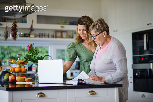 Portrait of woman with senior mother sitting indoors at home, using laptop. - gettyimageskorea