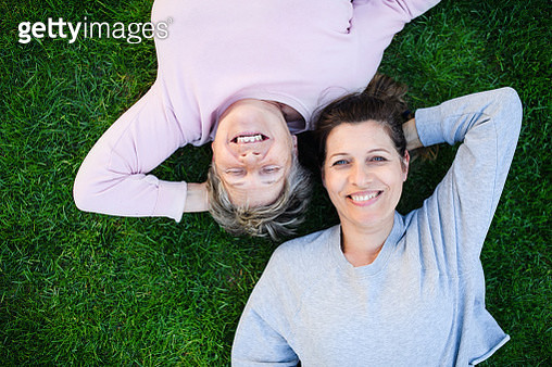 Top view portrait of woman with senior mother lying on grass outdoors, looking at camera. - gettyimageskorea