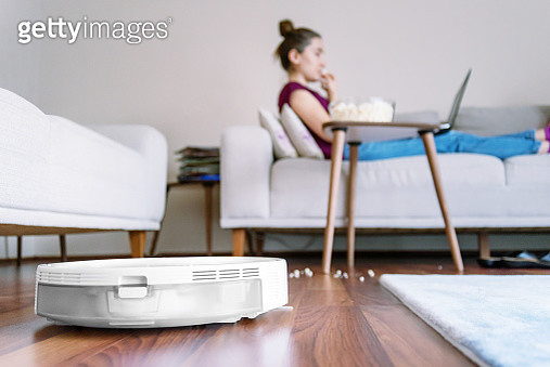 Wide view shoot of a woman relaxing and eating popcorns while a robotic vacuum cleaner working - gettyimageskorea