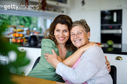 Portrait of woman with senior mother indoors at home, looking at camera. - gettyimageskorea