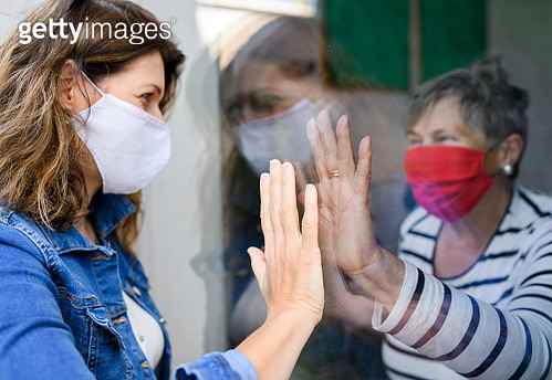 Woman with face mask greeting senior mother through glass, quarantine concept. - gettyimageskorea