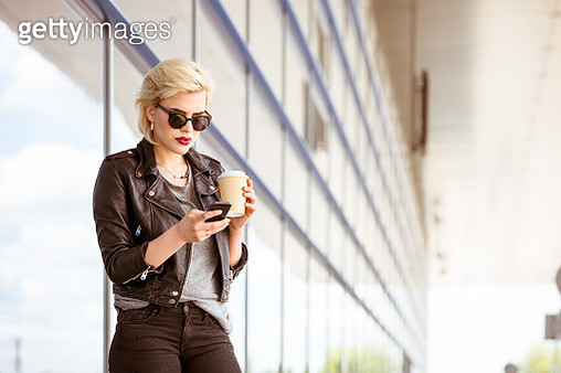 Fashionable young woman using phone at airport - gettyimageskorea