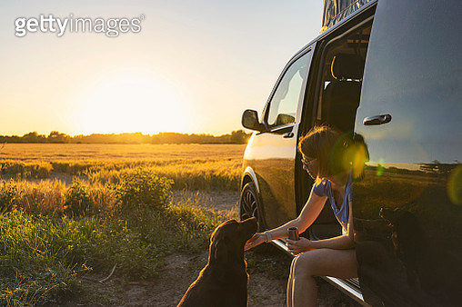 Woman and her pet dog at sunset - gettyimageskorea