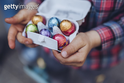 The hands of a unrecognizable little boy holding a box of chocolate Easter eggs - gettyimageskorea