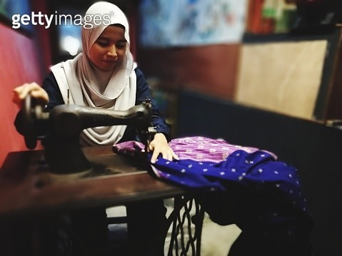 Female Tailor In Hijab Using Sewing Machine - gettyimageskorea