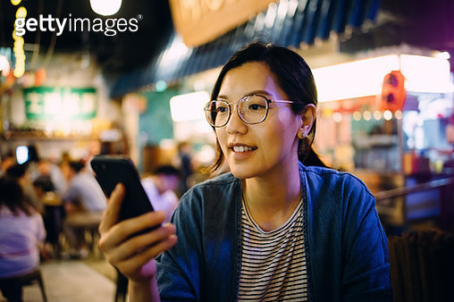 Young woman using smartphone in a traditional style restaurant - gettyimageskorea