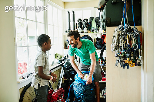 Smiling father packing backpack with son in gear room in home - gettyimageskorea
