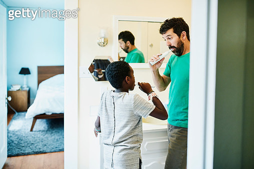Father and son brushing teeth in bathroom in home - gettyimageskorea