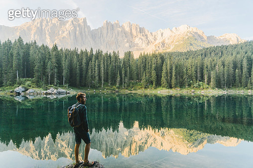 Young Caucasian man standing and looking at  Lago di Carezza in Dolomites - gettyimageskorea