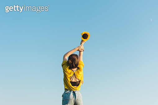 Low Angle View Of Woman Holding Sunflower Against Sky - gettyimageskorea