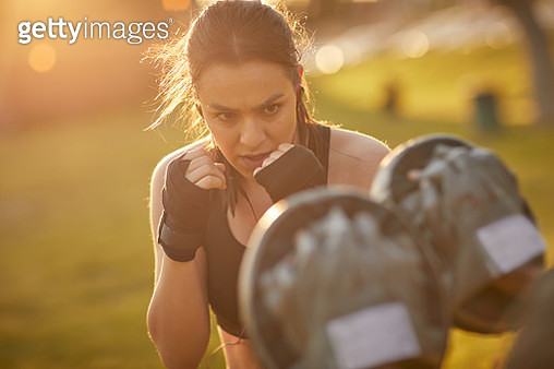 A young woman prepares to punch her target - gettyimageskorea