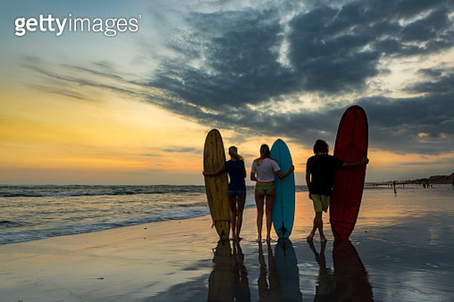 Facing the sunset along the coastline of a beach, a group of three people watch the horizon and hold their surfboard. Concept of team spirit and togetherness. - gettyimageskorea