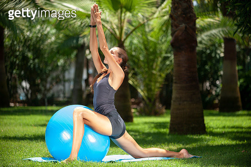 Young woman exercising and stretching her bodiy with pilates ball in the hotel garden - gettyimageskorea