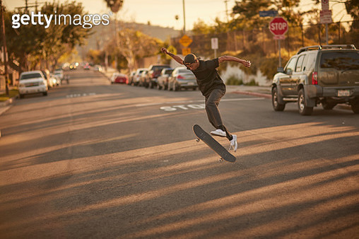 A young man does a trick on his skateboard on a city street - gettyimageskorea