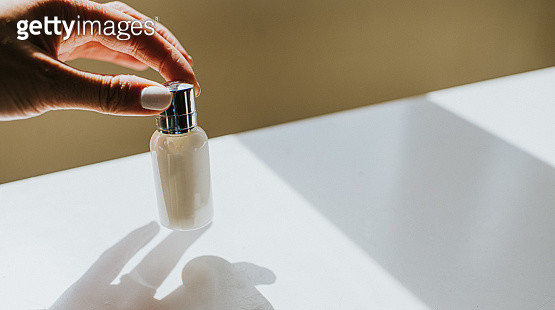 Hand pinching a plain bottle with silver top - gettyimageskorea