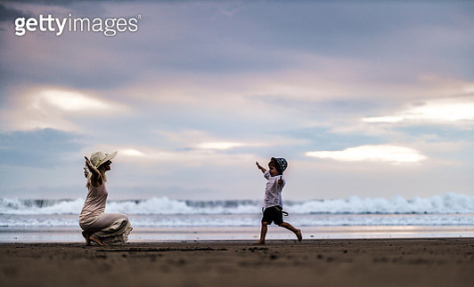 Happy little boy having fun while running into his mothers' embrace on the beach. Copy space. - gettyimageskorea