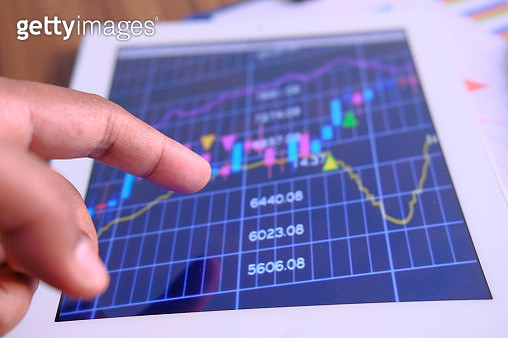 analyzing stock market charts on I pad - gettyimageskorea
